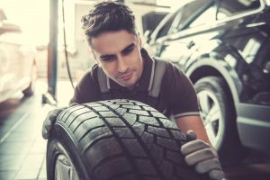 Handsome,Young,Auto,Mechanic,In,Uniform,Is,Examining,A,Tire